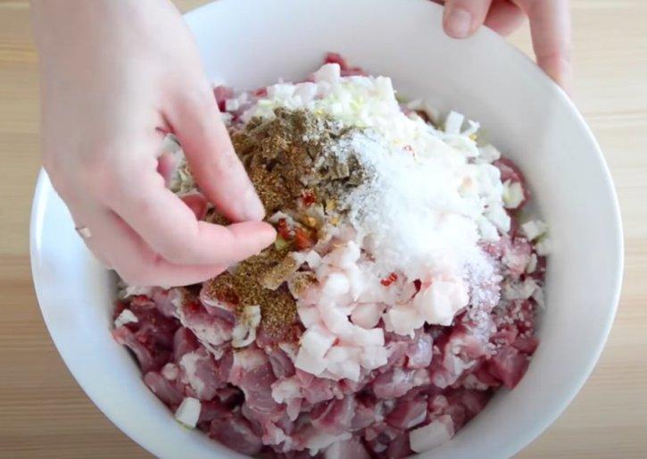 Добрый день! Домашние колбаски из свинины абсолютно натуральный и уникальный продукт. Это блюдо традиционно готовят в разных странах мира, особенно популярны колбаски в Восточной Европе. В основном рецепты колбасок в разных регионах очень схожи, но каждая хозяйка старается добавить в блюдо неповторимую изюминку. Например, можно включить в состав колбасы немного коньяка, вина, сухофруктов или орехов. Я готовлю домашние колбаски по рецепту моей бабушки. Сделать их в домашних условиях гораздо проще, чем это может показаться на первый взгляд. Это блюдо я всегда делаю из свинины, но можно использовать говядину, дичь и домашнюю птицу. Особенно вкусной получается домашняя колбаса из таких частей мяса как окорок, лопатка и шейная часть. Рекомендую готовить из жирного мяса, так как продукт должен состоять минимум на 20% из жира. Оболочки для колбас могут быть искусственными или натуральными – мне предпочтительнее последний вариант. Для маленьких колбасок лучше использовать овечьи кишки, а для больших колбас свиные оболочки. Я покупаю их уже в готовом виде: оболочки уже пропитаны соляным раствором и промыты. Если таковых нет, то их нужно очистить самостоятельно и замочить на ночь в воде с большим содержанием соли. Также для колбас можно использовать синтетические оболочки из коллагена, которые не нужно вымачивать в соленой воде. Ингредиенты: 1,5 кг свинины; 200-300 г сала без мясной прослойки; 200 мл кипяченой воды; 2 ч. ложки морской соли; 1 ч. ложка молотого черного перца; 1 ч. ложка сушеного кориандра; 1-2 сушеных острых перцев чили; 3-5 долек чеснока; 3 м натуральной оболочки (кишки). Рецепт домашних колбасок в натуральной оболочке из свинины Приготовление: Шаг 1. В первую очередь я промываю натуральную оболочку, несмотря на то, что она уже продается в магазине очищенной. Легче всего кишки промыть получается, надев каждую на кран с водой. Я пускаю прохладную воду внутрь оболочки, и она там хорошо промывается.=1 Шаг 2. Дополнительно ополаскиваю кишки с наружной стороны. За
